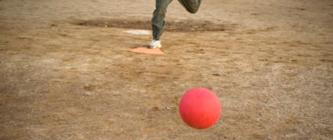 A kickball rolling on the ground.