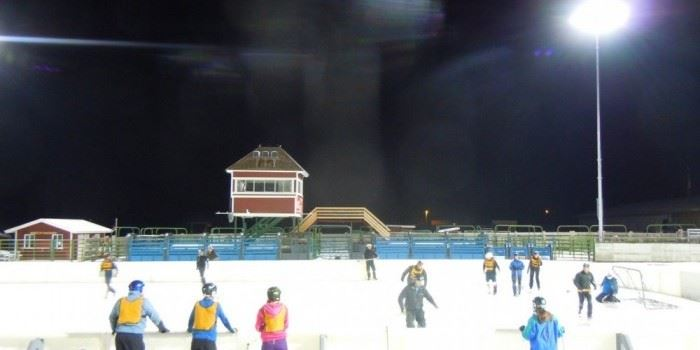 People ice skating on an outdoor ice rink.