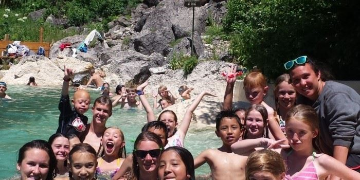 A group of kids swimming outside in hot springs.
